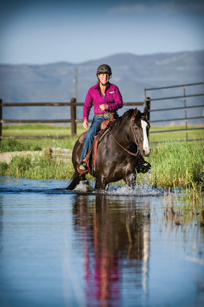 Julie riding Dually in the pond, Cosequin shirt on.